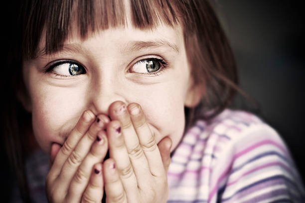 Cute little girl laughing and covering mouth Beautiful little girl covering mouth, laughing. Fingernails partially covered with purple peeling paint. desaturated stock pictures, royalty-free photos & images