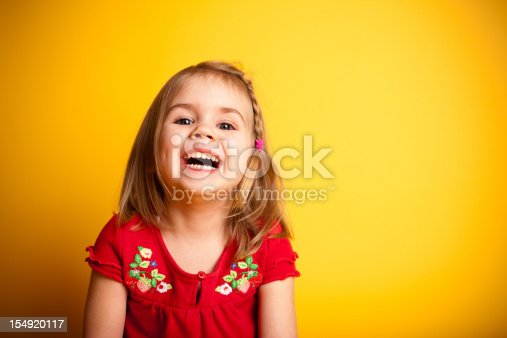Color image of a little girl laughing while looking at the camera and isolated on yellow background.
