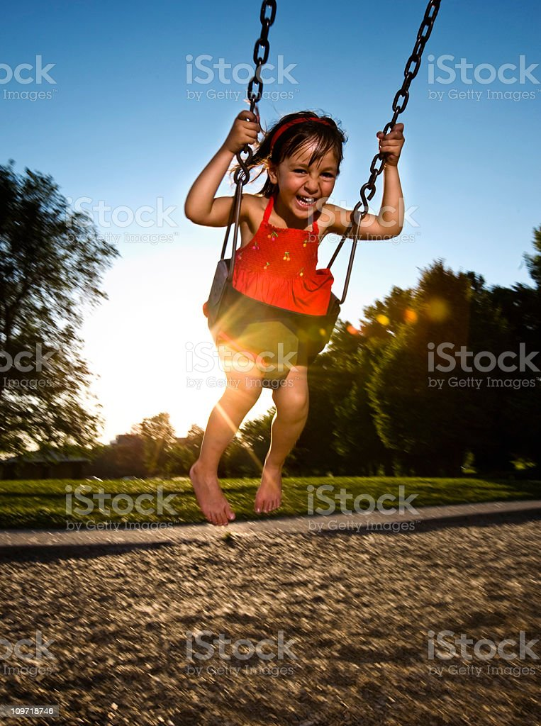 Cute Little Girl Laughing While Swinging at Playground royalty-free stock photo