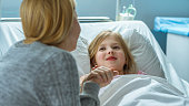istock Cute Little Girl Lies on a Bed in the Children's Hospital and Talking with Her Mother Sits Beside. Modern Pediatric Ward. 1038799646