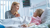 istock Cute Little Girl Lies on a Bed in the Children's Hospital, Her Mother Sits Beside, They Talk. Modern Pediatric Ward. 1038799602