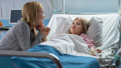 istock Cute Little Girl Lies on a Bed in the Children's Hospital, Her Mother Sits Beside, They Talk. Modern Pediatric Ward. 1038799672