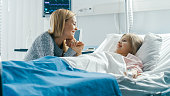 istock Cute Little Girl Lies on a Bed in the Children's Hospital, Her Mother Sits Beside, They Talk. Modern Pediatric Ward. 1038799798