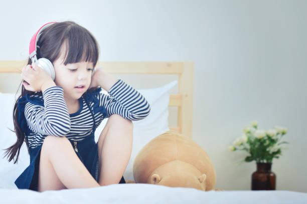 Niedliche kleine Mädchen Musik hören mit Kopfhörer. – Foto