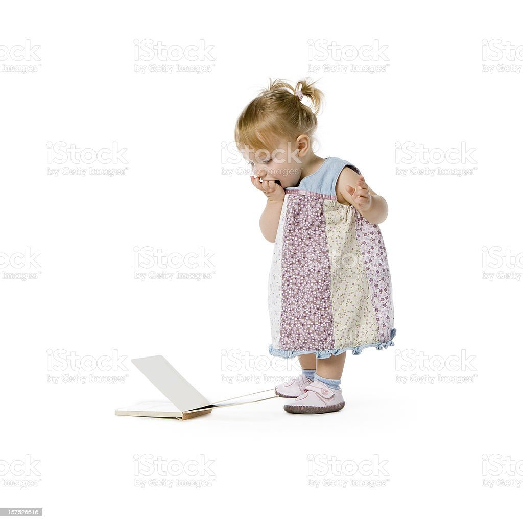 Cute little girl looking at a book on floor royalty-free stock photo