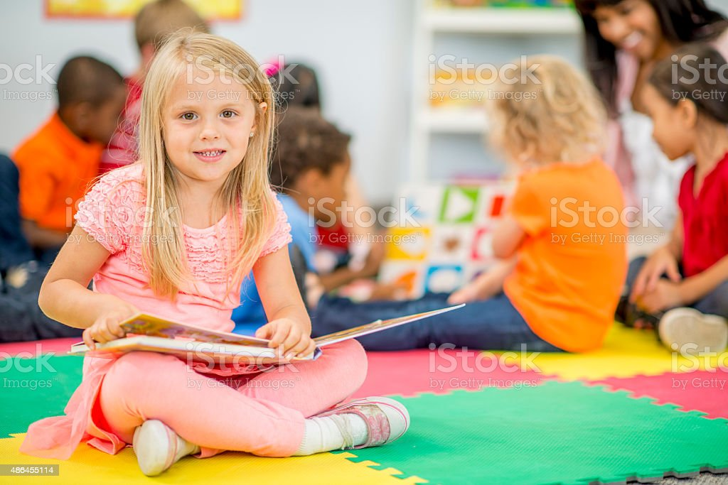 Cute Little Girl Looking at Picture Book stock photo
