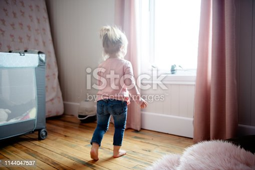 Portrait of a cute little girl looking through the window in her bedroom. Photo was taken in Quebec Canada