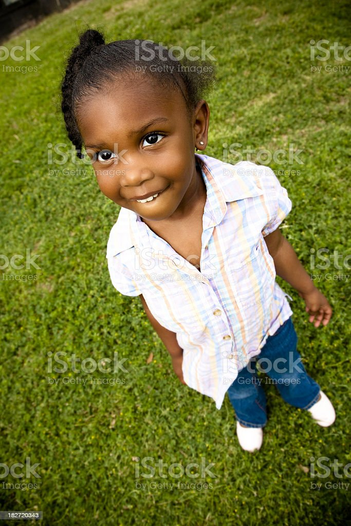 Cute Little Girl Looking Up on Green Grass royalty-free stock photo
