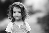 Little girl with brown hair outdoors, looking up in curiosity; monochrome shot