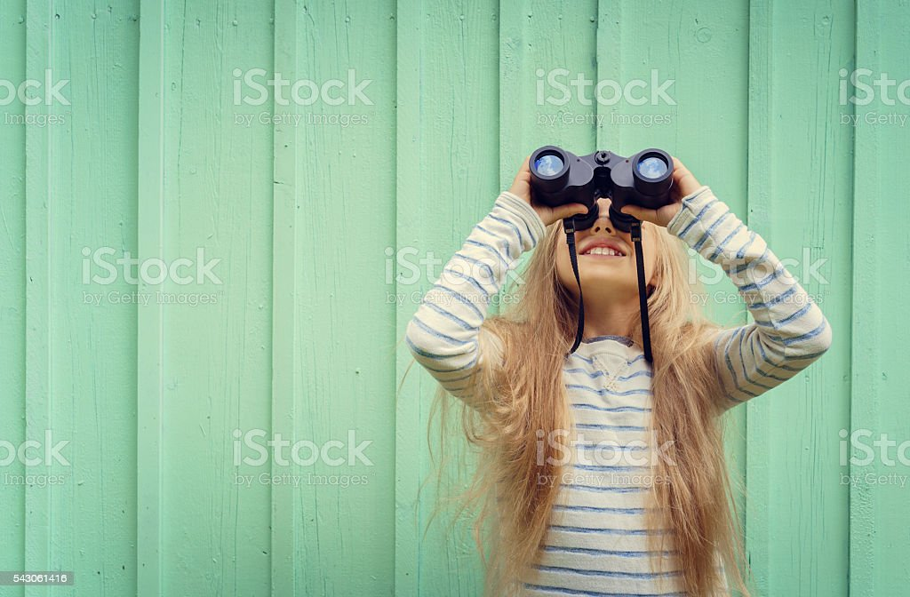 Cute little girl looks binoculars. Space for text stock photo