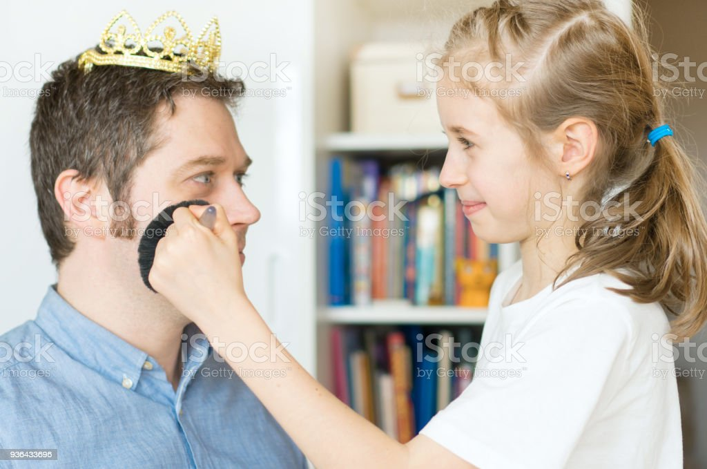Cute little girl making makeup to her dad. - Stock image .