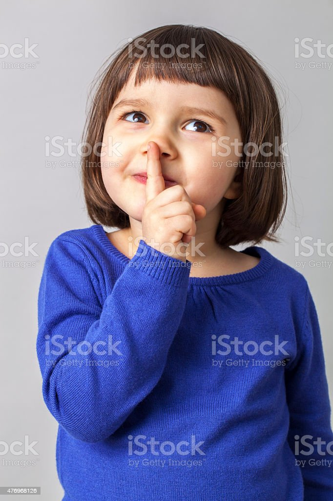 cute little girl making the sign for keeping a secret stock photo