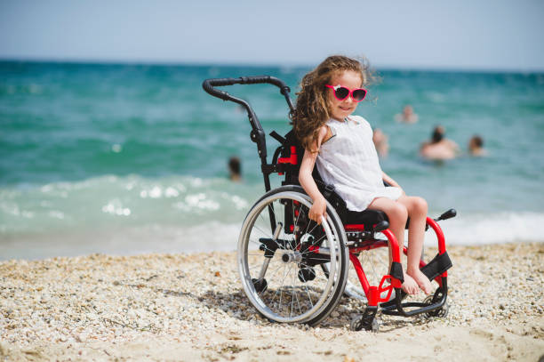 Cute little girl  on the wheelchair by the sea Cute little girl  on the wheelchair by the sea sonderjylland stock pictures, royalty-free photos & images