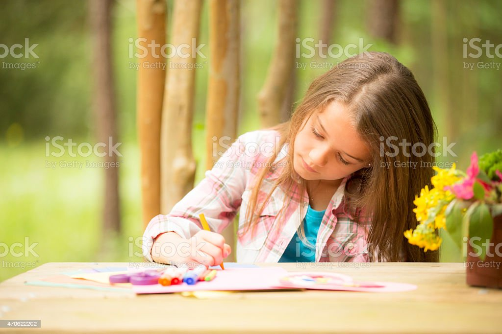 Cute little girl outdoors making Father's Day card. Child, backyard. stock photo