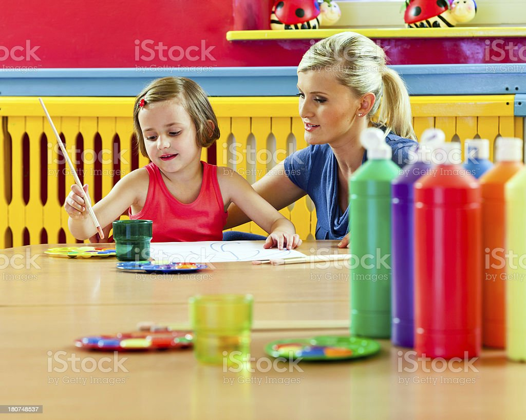 Cute Little Girl Painting A cute preschool girl sitting at the table in classroom and painting, teacher watching her work. Focus on background. 20-24 Years Stock Photo