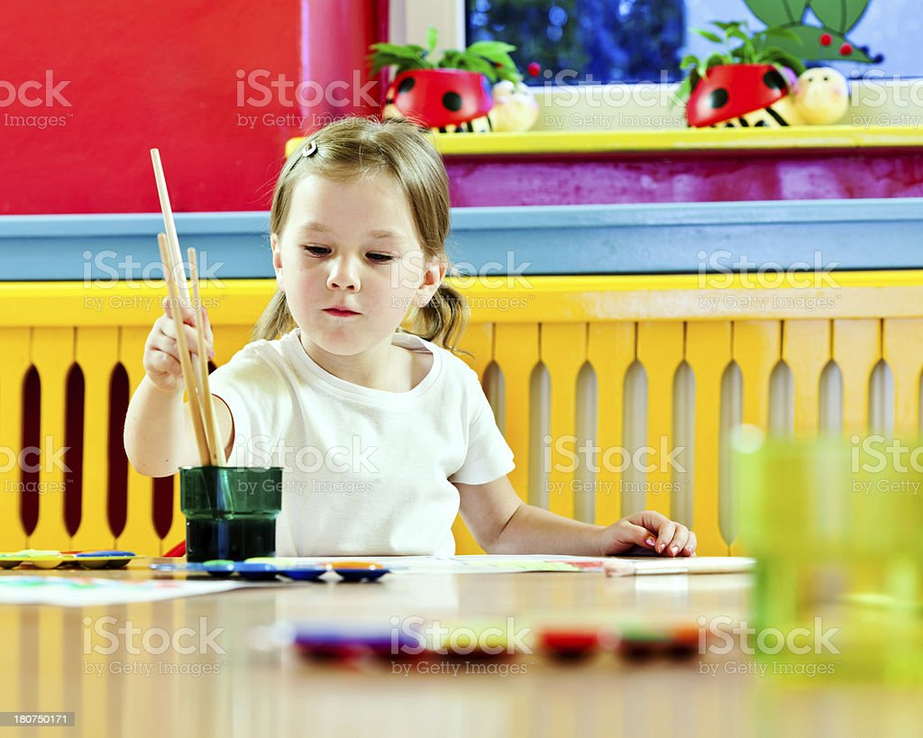 Cute Little Girl Painting A cute preschool girl sitting at the table in classroom and painting. Focus on background. 4-5 Years Stock Photo