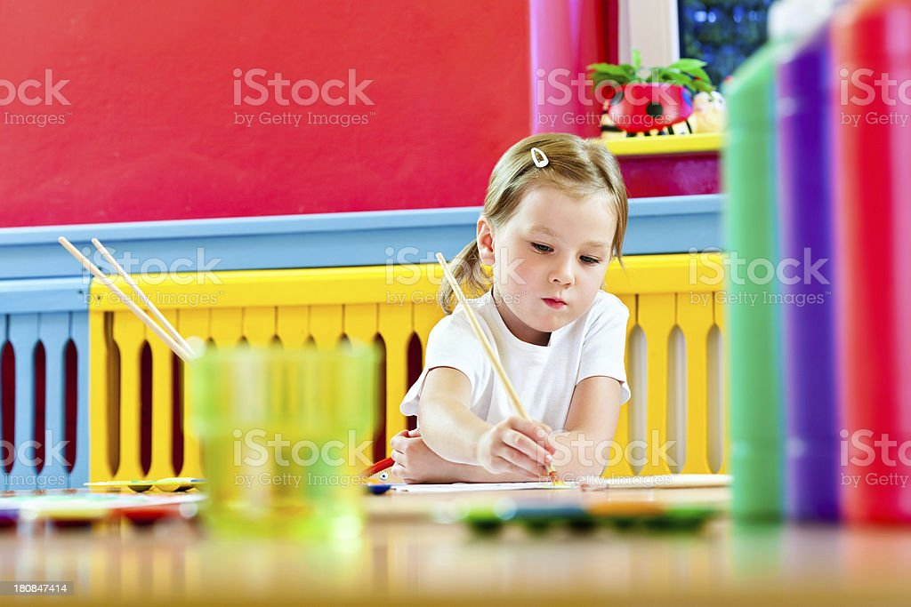 Cute Little Girl Painting A cute preschool girl sitting at the table in a playroom and painting. Focus on background. 4-5 Years Stock Photo