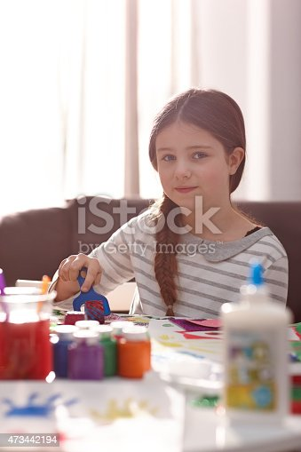 123499844 istock photo Cute little girl painting while sitting at table 473442194