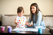 istock cute little girl painting with mommy together at home, portrait of mother and daughter painting at home 1142677936