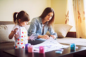 istock cute little girl painting with mommy together at home, portrait of mother and daughter painting at home 1142677947