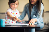 istock cute little girl painting with mommy together at home, portrait of mother and daughter painting at home 1142677968