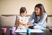 istock cute little girl painting with mommy together at home, portrait of mother and daughter painting at home 1142678032