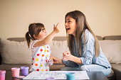 istock cute little girl painting with mommy together at home, portrait of mother and daughter painting at home 1142678081