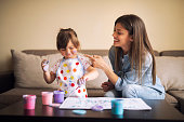 istock cute little girl painting with mommy together at home, portrait of mother and daughter painting at home 1142678126