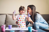 istock cute little girl painting with mommy together at home, portrait of mother and daughter painting at home 1142678145
