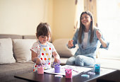 istock cute little girl painting with mommy together at home, portrait of mother and daughter painting at home 1142678155
