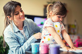 istock cute little girl painting with mommy together at home, portrait of mother and daughter painting at home 1142678164