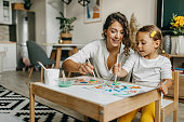 istock Cute little girl painting with mummy 1277804038