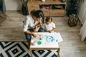 istock Cute little girl painting with mummy 1277804163