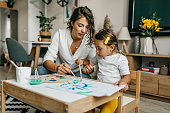 istock Cute little girl painting with mummy 1277804165