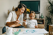 istock Cute little girl painting with mummy 1277804168