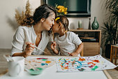 istock Cute little girl painting with mummy 1277804188
