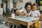 istock Cute little girl painting with mummy 1277804286
