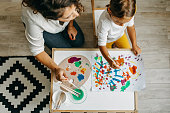 istock Cute little girl painting with mummy 1277804359
