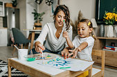istock Cute little girl painting with mummy 1277804405