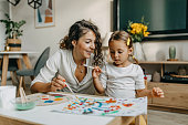 istock Cute little girl painting with mummy 1277804436
