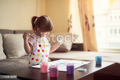 istock cute little girl painting with paintbrush and colorful paints. 1142678095