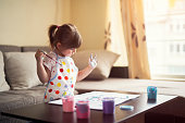 Little cute girl painting at home with colorful paints.