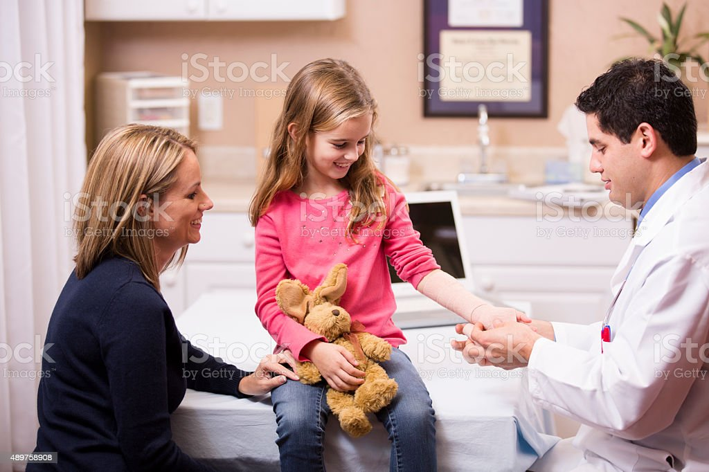 Cute little girl patient with pediatrician doctor, mother. Latin descent. stock photo