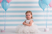 Cute little girl in fluffy white dress is looking at camera while sitting near balloons, on light background