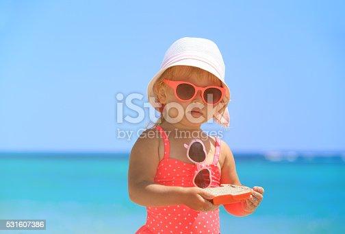 istock cute little girl play on sand beach 531607386