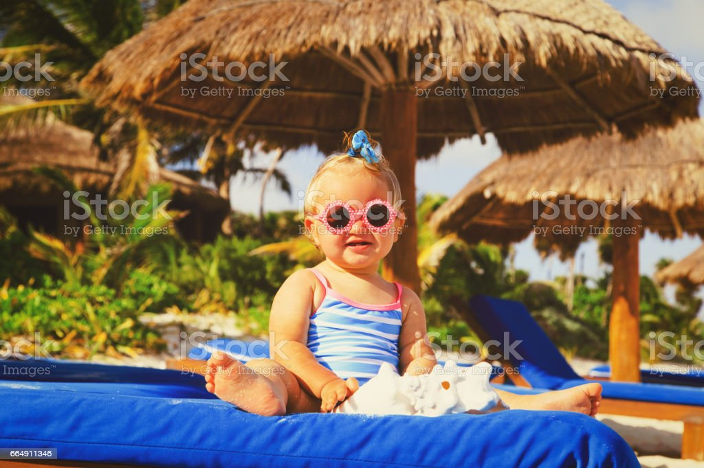 cute little girl play with seashells on beach foto stock royalty-free