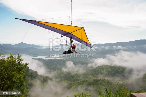 A cute little girl is playing a paragliding, close-up shots with the clear sky and foggy valley as background. Yogyakarta, Indonesia - January 26, 2020.