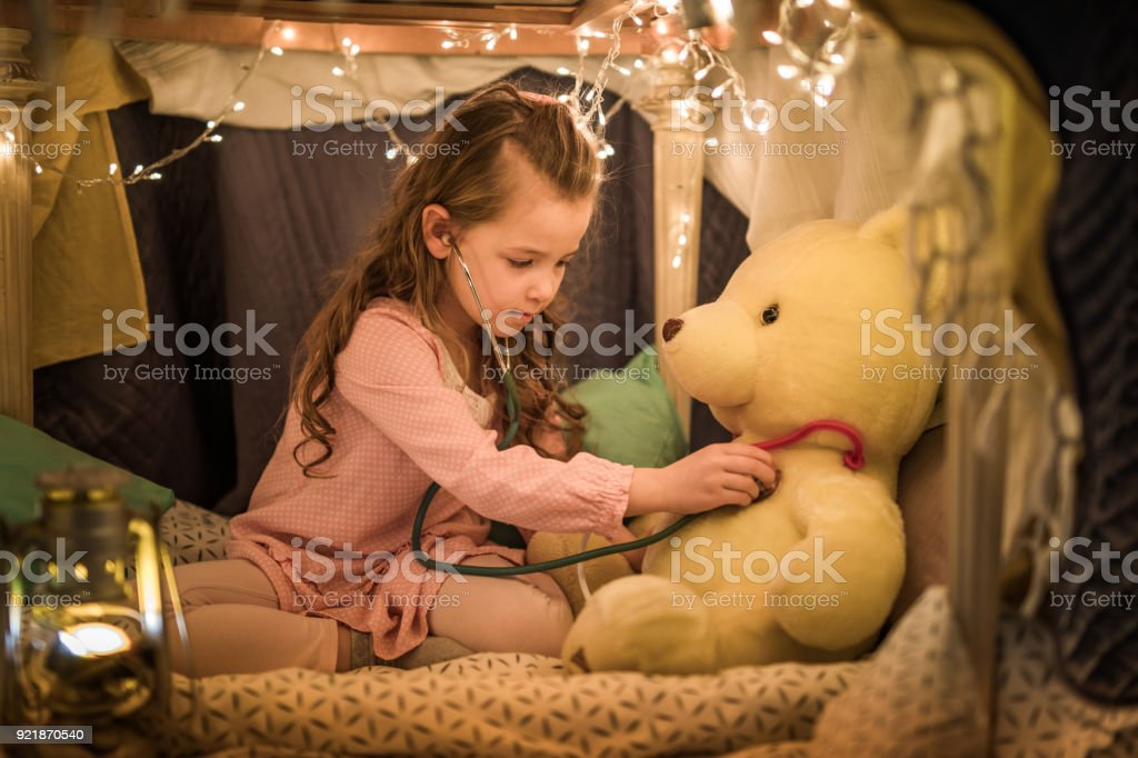 Cute little girl playing doctor with her teddy bear in a tent at home. stock photo