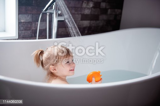 Cute little girl of 2-3 years old playing in a bathtub. Photo was taken in Quebec Canada