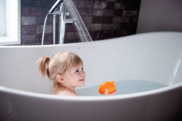 Cute little girl playing in a bathtub Cute little girl of 2-3 years old playing in a bathtub. Photo was taken in Quebec Canada kids cleaning up toys stock pictures, royalty-free photos & images
